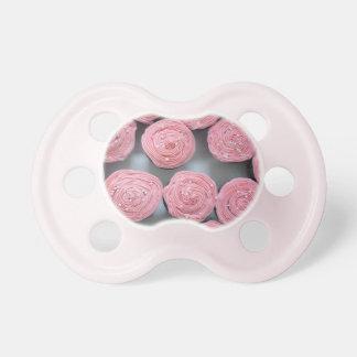 Las magdalenas rosadas de la fresa asperjan el chupete de bebe
