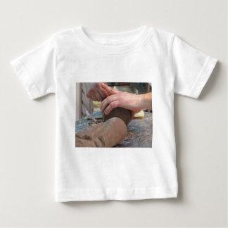 Las manos cortaron una escultura de un chocolate camiseta de bebé
