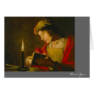 Lectura del hombre joven por luz de una vela tarjeta de felicitación
