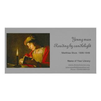 Lectura del hombre joven por luz de una vela tarjeta fotografica