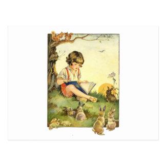 Lectura del muchacho debajo del árbol con los postal