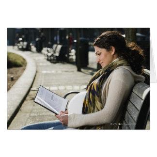 Lectura medio-oriental embarazada de la mujer en p felicitación