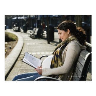 Lectura medio-oriental embarazada de la mujer en p postal