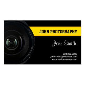 Lente y tarjeta de visita amarilla de la fotografí