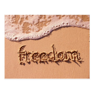 Libertad escrita dentro de la arena entre las postal