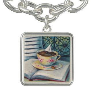 Libro de la taza de té y pulsera con dije de plata