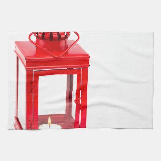 Linterna roja con el tealight ardiente en blanco paño de cocina