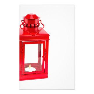 Linterna roja con el tealight ardiente en blanco papelería