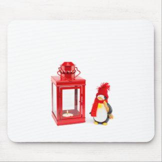 Linterna roja con la estatuilla del pingüino en alfombrilla de ratón