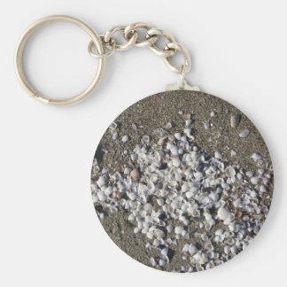 Llavero Seashells en la arena. Fondo de la playa del