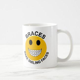 Los apoyos hacen la taza de café sonriente de las