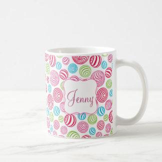 Los caramelos rayados divertidos en colores en taza de café