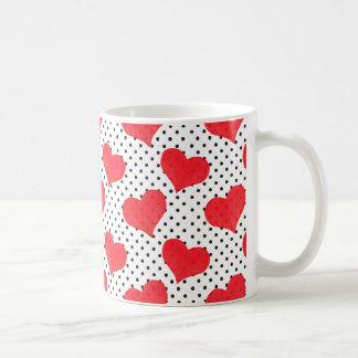 Los corazones rojos en un negro puntean el fondo taza de café