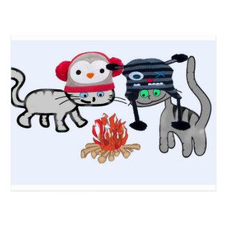 Los gatos disfrutan del calor del fuego postal