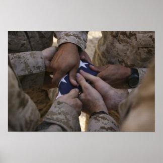Los infantes de marina doblan una bandera póster