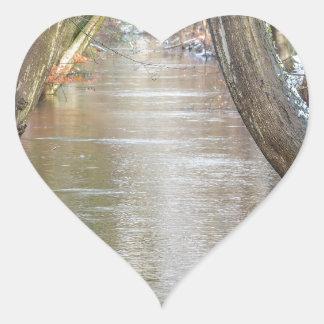 Los troncos y el bosque de árbol fluyen con nieve pegatina en forma de corazón