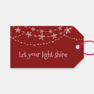 Luces de navidad en etiqueta roja del regalo del