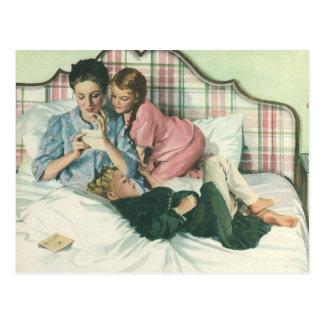 Madre y niños del vintage que leen tarjetas en postal