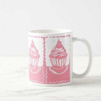 Magdalenas rosadas con la taza de la frontera de