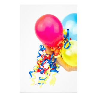 Mano que da los globos coloridos con las cintas papelería