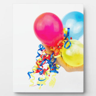 Mano que da los globos coloridos con las cintas placa expositora