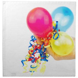 Mano que da los globos coloridos con las cintas servilleta de tela