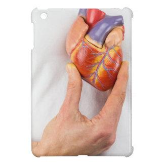 Mano que lleva a cabo el corazón modelo en pecho