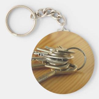 Manojo de llaves gastadas de la casa en la tabla llavero redondo tipo chapa