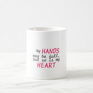 Manos por completo, taza llena del corazón