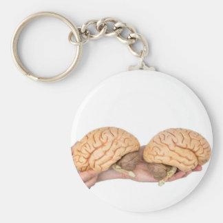 Manos que sostienen el cerebro humano modelo en llavero
