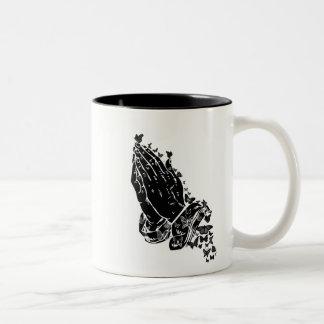 Manos y taza de rogación de las mariposas