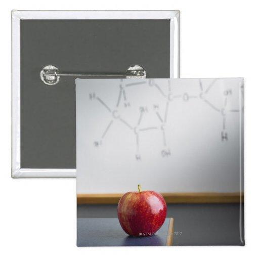 Manzana roja que se sienta en el escritorio de los pins