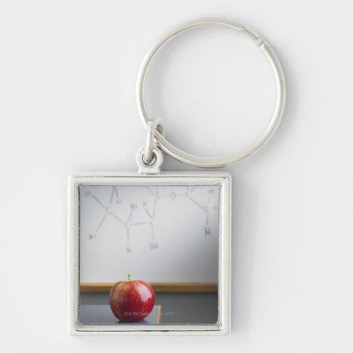 Manzana roja que se sienta en el escritorio de los llaveros personalizados