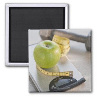 Manzana verde en escala del peso, cinta métrica y imán de frigorifico