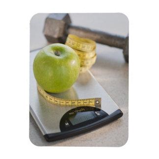 Manzana verde en escala del peso, cinta métrica y imán de vinilo