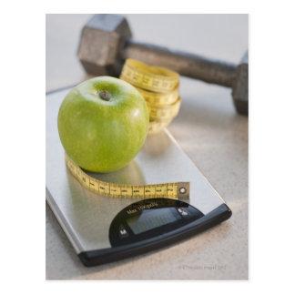 Manzana verde en escala del peso, cinta métrica y postal