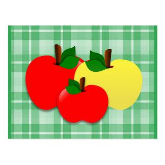 Manzanas rojas y amarillas en la tela escocesa a postal
