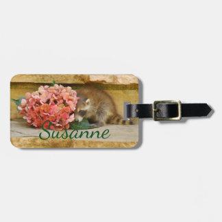 Mapache tímido del bebé detrás del ramo floral etiqueta para maletas
