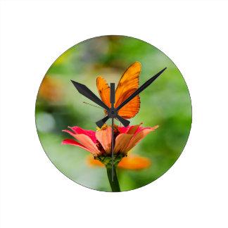 Mariposa brillante en la margarita anaranjada reloj redondo mediano