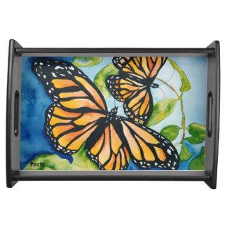 Mariposas de monarca que sirven la bandeja