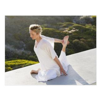 Mediados de ejercicio practicante de la yoga de la postal