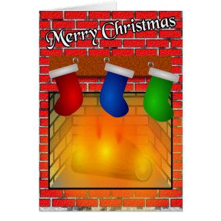 Medias sobre una tarjeta de Navidad de la chimenea