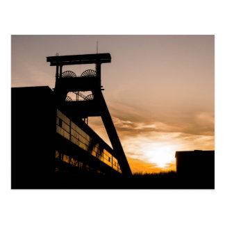 Mina de carbón en la puesta del sol postal