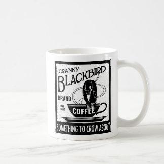 Mirlo de cuervo del negro de la taza de la