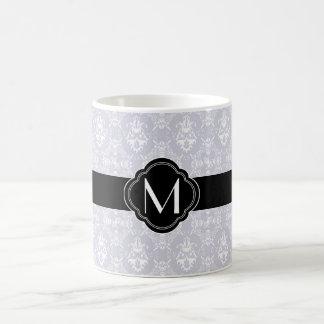 Modelo gris delicado del damasco con el monograma taza de café