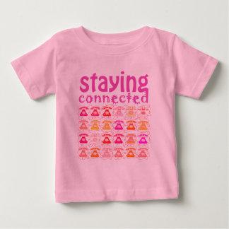 Modelo rosado del teléfono que permanece la camiseta de bebé