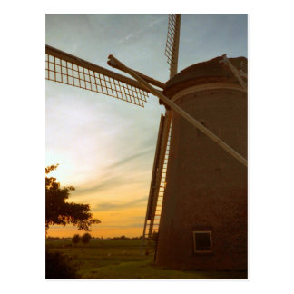 Molino de viento en la puesta del sol postal