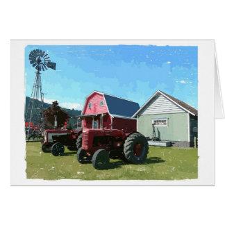 Molino de viento, tractores antiguos y edificios tarjeta