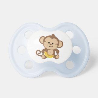 Mono del muchacho con el plátano chupete