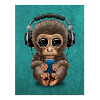 Mono lindo del bebé con el auricular que lleva del postal